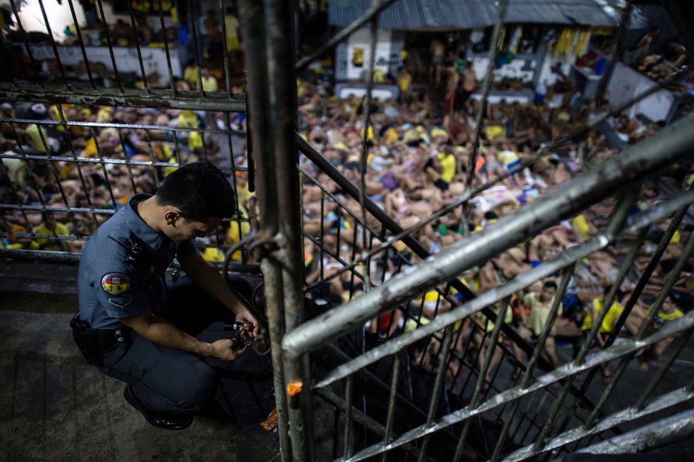 A prison guard locks a gate inside the Quezon City jail at night in Manila in this picture taken on July 21, 2016. There are 3,800 inmates at the jail, which was built six decades ago to house 800, and they engage in a relentless contest for space. Men take turns to sleep on the cracked cement floor of an open-air basketball court, the steps of staircases, underneath beds and hammocks made out of old blankets. / AFP / NOEL CELIS / TO GO WITH AFP STORY: Philippines-politics-crime-jails, FOCUS by Ayee Macaraig (Photo credit should read NOEL CELIS/AFP/Getty Images)