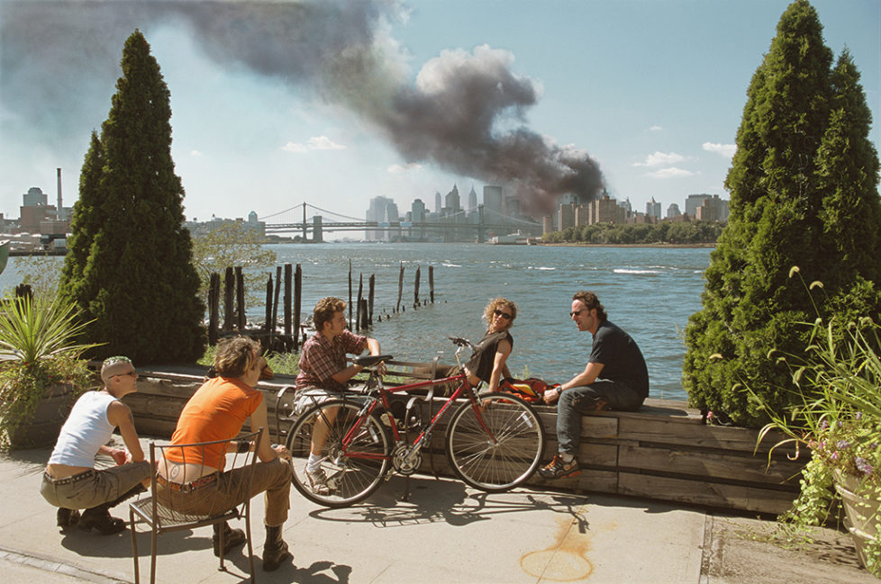 USA. Brooklyn, New York. September 11, 2001. Young people relax during their lunch break along the East River while a huge plume of smoke rises from Lower Manhattan after the attack on the World Trade Center. (KEYSTONE/MAGNUM PHOTOS/Thomas Hoepker)