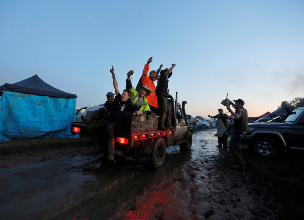 """Men ride on the back of a truck driving through mud on the final night of the Deni Ute Muster in Deniliquin, New South Wales, Australia, October 1, 2016. REUTERS/Jason Reed SEARCH """"UTE CULTURE"""" FOR THIS STORY. SEARCH """"THE WIDER IMAGE"""" FOR ALL STORIES."""