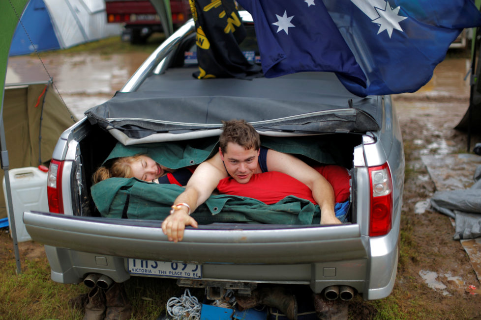 """Australian couple Darren McGarvie, 27, and Nicole York, 24, wake up after spending the night together in McGarvie's Holden Commodore Ute at the Deni Ute Muster in Deniliquin, New South Wales, Australia, October 1, 2016. REUTERS/Jason Reed SEARCH """"UTE CULTURE"""" FOR THIS STORY. SEARCH """"THE WIDER IMAGE"""" FOR ALL STORIES."""