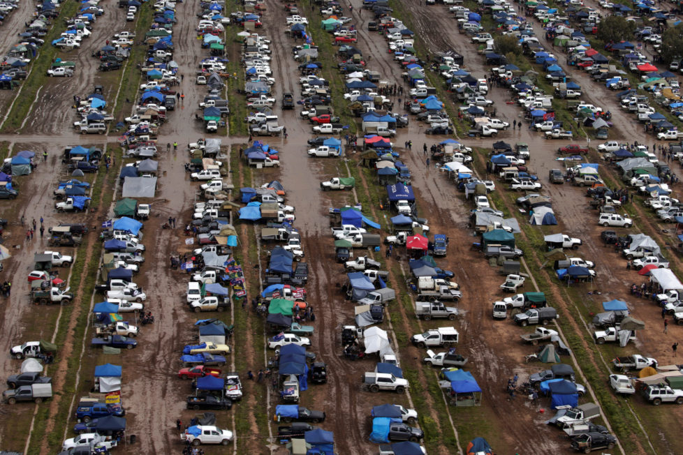 """Campers trudge through mud among hundreds of ute vehicles in a paddock in this aerial picture at the Deni Ute Muster in Deniliquin, New South Wales, Australia, October 1, 2016. REUTERS/Jason Reed SEARCH """"UTE CULTURE"""" FOR THIS STORY. SEARCH """"THE WIDER IMAGE"""" FOR ALL STORIES."""