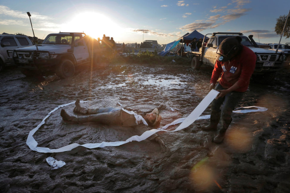 """Jess Elderedge makes a 'mud angel' as a friend lays toilet paper around her during a party at sunset on the final night of the Deni Ute Muster in Deniliquin, New South Wales, Australia, October 1, 2016. REUTERS/Jason Reed SEARCH """"UTE CULTURE"""" FOR THIS STORY. SEARCH """"THE WIDER IMAGE"""" FOR ALL STORIES."""
