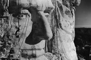 American sculptor Gutzon Borglum (1867 - 1941) (hanging below the eye) and several of his crew work on carving the head of American President Abraham Lincoln, part of the Mount Rushmore National Memorial, Keystone, South Dakota, 1930s. Lincoln's head, the third head carved, was completed and dedicated on September 17, 1937. (Photo by Frederic Lewis/Getty Images)