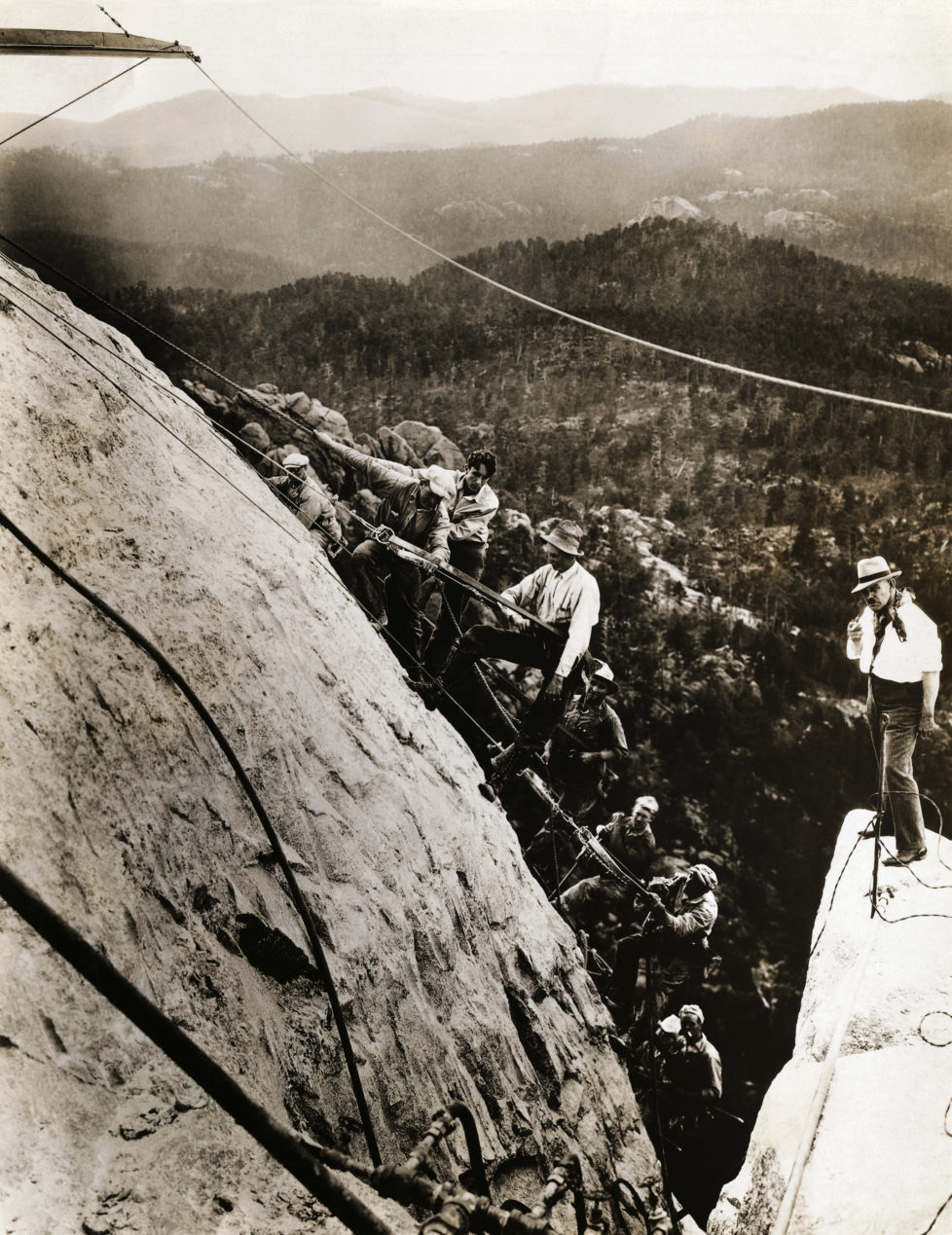 American sculptor Gutzon Borglum (r), who is leading the Mount Rushmore National Memorial project, stands on top of Mount Rushmore with a gang of his sculptors, finishing and smoothing the great granite cliff that will form part of the memorial. The sculptors are standing on the section which will become the forehead of George Washington. (Photo by George Rinhart/Corbis via Getty Images)