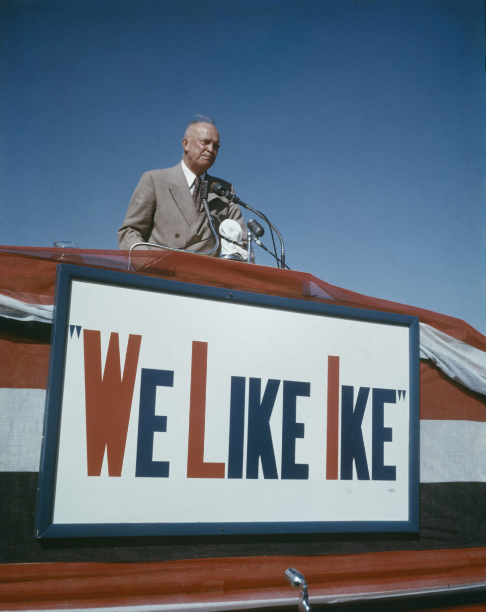 American General Dwight D Eisenhower (1890-1969) speaks on a podium above a sign declaring 'We Like Ike' during his presidential election campaign in Lubbock, Texas in October 1952. (Photo by Rolls Press/Popperfoto/Getty Images) *** Local Caption *** Dwight D. Eisenhower