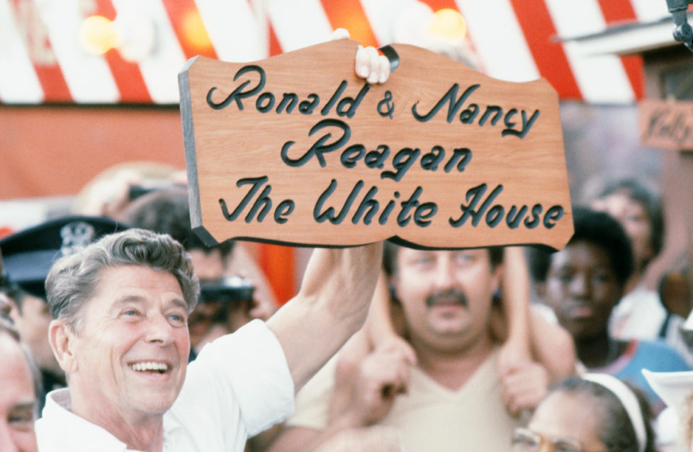 During his presidential campaign, American politician (and future US President) Ronald Reagan (1911 - 2004) holds up a personalized wooden sign at the Michigan State Fair, Ionia, Michigan, August 8, 1980. The sign reads 'Ronald & Nancy Reagan; The White House' with the lettering burning into a piece of cut wood. (Photo Robert R. McElroy/Getty Images)