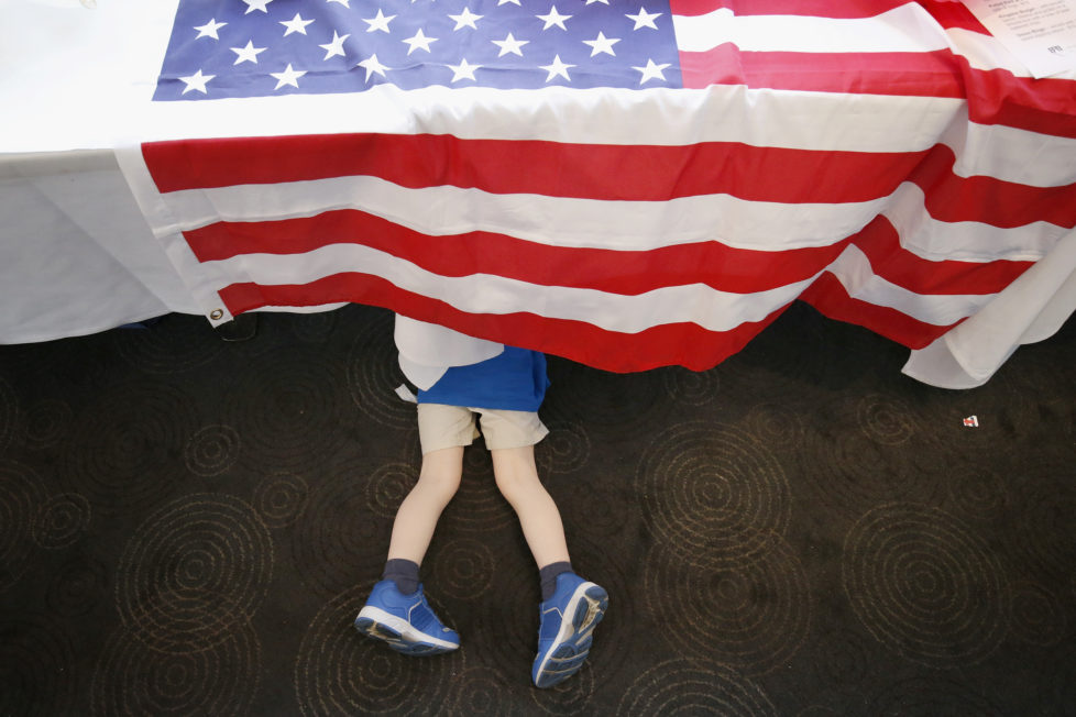 MELBOURNE, AUSTRALIA - NOVEMBER 09: A young boy plays under a table during a 'Democrats Abroad' function at the Kingston Hotel on November 9, 2016 in Melbourne, Australia. There has been huge interest in the U.S. Election between Hillary Clinton and Donald Trump in Australia, with many people arranging viewing parties around the country to watch the results live. (Photo by Darrian Traynor/Getty Images)