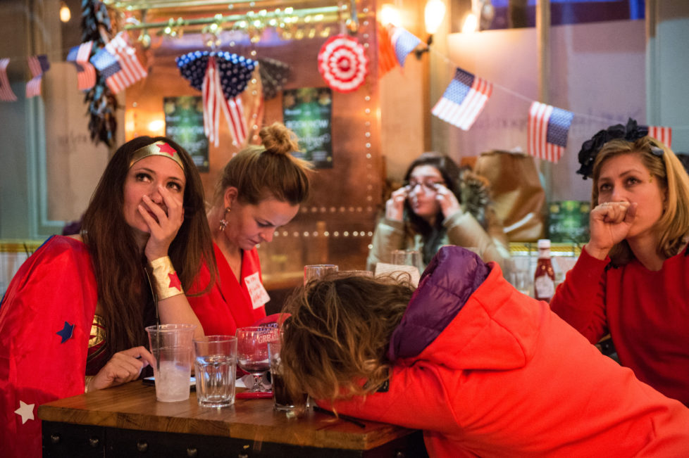 LONDON, ENGLAND - NOVEMBER 09: American Democratic Party supporters, one in a Wonder Woman costume, react to the news that Donald Trump has won the state of Florida at the Democrats Abroad election night party at Marylebone Sports Bar and Grill on November 9, 2016 in London, England. Americans go to the polls today to choose between Trump and Democrat Hillary Clinton for president. (Photo by Chris J Ratcliffe/Getty Images)
