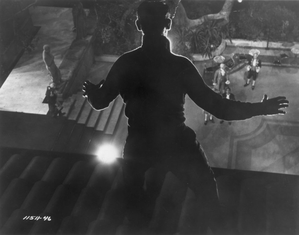 1955: Thief Cary Grant (1904 - 1986) stands frozen in the light as he is spied on the roof in a scene from Hitchcock's film 'To Catch A Thief'. (Photo by Hulton Archive/Getty Images)