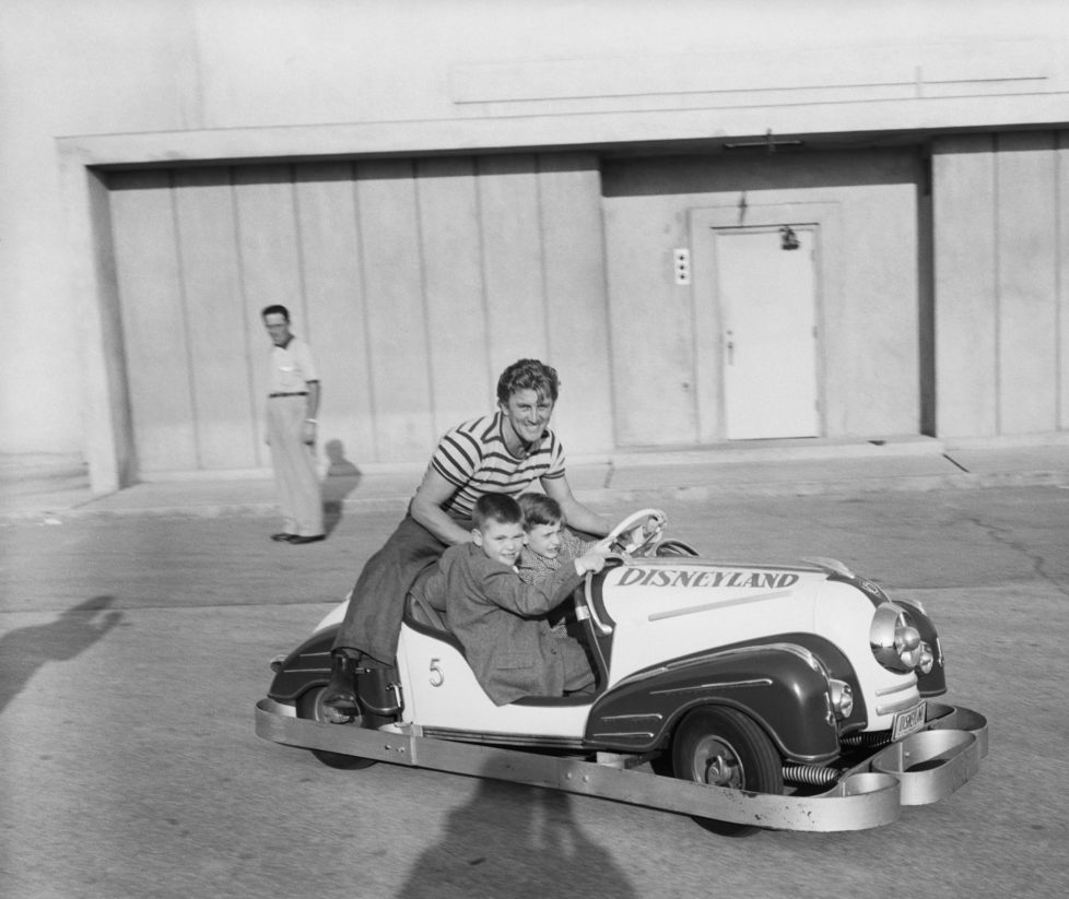 Kirk Douglas shares some automotive thrills with his two sons, Joel (left) and Michael (right), in one of the miniature roadsters at Disneyland. Producer Walt Disney has planned a $9,000,000 project showing the land of the future, and a highlight is to be a miniature freeway in which the youngsters will drive model cars.